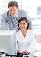 Attractive businesswoman working at a computer with her manager in the office