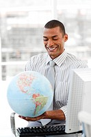 Smiling businessman holding aterrestrial globe in the office