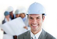 Smiling arhitect with a hardhat in front of his team