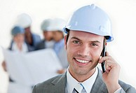 Smiling arhitect with a hardhat on phone in front of his team