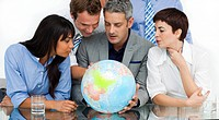 International business people looking at a terrestrial globe in the office