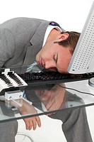 Tired businessman sleeping on his desk against a white background