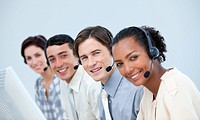 Smiling business people using headset in a call center