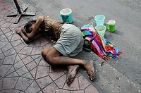 Poor Beggar sleeping on a Street in Bangkok , Thailand