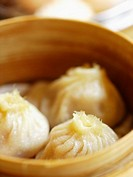 Close_up of steamed xiaolongbao in a steamer basket