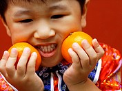 Close_up of a boy holding oranges and clenching his teeth