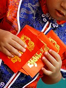 Close_up of a boy holding red gift packets Hong Bao
