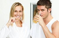 Woman holding pills and man drinking orange juice in bathroom