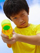 Portrait of a boy aiming a squirt gun