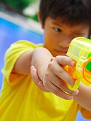 Close_up of a boy aiming a squirt gun