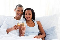 Romantic couple toasting with Champagne lying on their bed