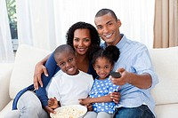Smiling Afro_american family eating popcorn and watching TV in the living_room