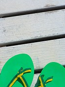 Close_up of a pair of flip_flops on a pier