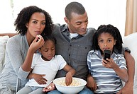 Afro_American family watching a film at home and earting popcorn