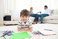 Smiling child drawing lying on the floor in the living room