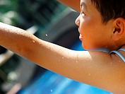Rear view of a boy at the poolside with his arms raised