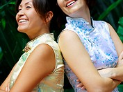Portrait of two women standing back to back and smiling
