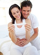 Smiling couple finding out results of a pregnancy test sitting on bed