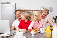 Lively family having breakfast together in the kitchen