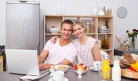 Young couple using a laptop while having breakfast in the kitchen