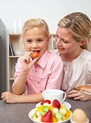Attractive mother eating fruit with her daughter in the kitchen