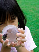 Close_up of a girl looking through a transparent globe