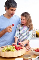 Cheerful father and his daughter having breakfast in the kitchen
