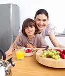 Happy mother and her child having breakfast in the kitchen