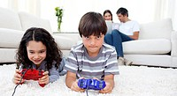 Adorable siblings playing video games lying on the floor with their parents in the background