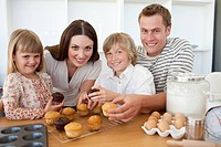Smiling family eating their muffins in the kitchen
