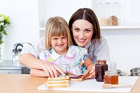 Attentive mother helping her daughter prepare the breakfast in the kitchen