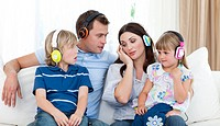Family listening music with headphones on the sofa
