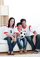 Jolly young family watching a football match at home