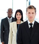 Confident brunette businesswoman in focus with her team