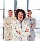 Smiling young businesswoman with her team in the background