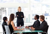 Attractive businesswoman smiling with folded arms in a meeting