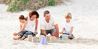 Happy family playing with the sand
