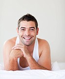 Smiling young man in bed