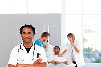 African doctor with folded arms looking at the camera with team in the backgroud