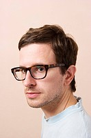 Young man with retro glasses looking at the camera.