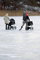 Rear view of two women ice_skating with their baby strollers