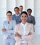 Multi _ethnic business team standing in office looking at the camera