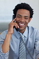Portrait of smiling Afro_American young businessman on phone in office