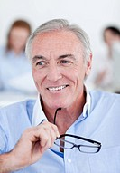 Smiling senior businessman holding glasses in an office