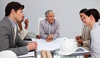 Group of architects studying plans in a meeting