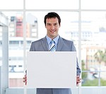 Portrait of a male manager holding a white board in the office