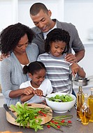 Affectionate family preparing salad together in the kitchen