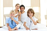 Jolly family singing together through microphones