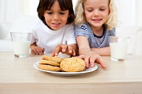 Adorable siblings eating biscuits in the kitchen