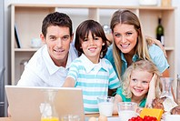 Loving family using laptop during the breakfast in the kitchen